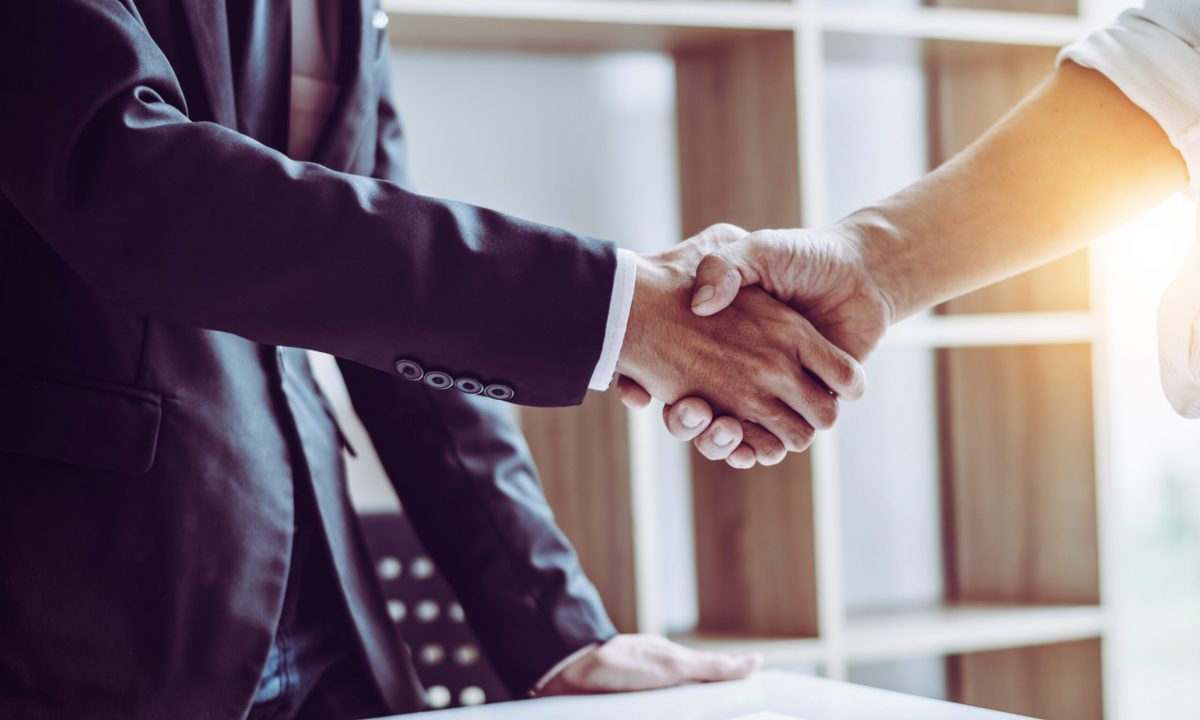 Middle age partner lawyers attorneys shaking hands after discussing a contract agreement done, Asian people.